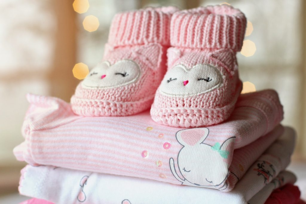pink baby socks with patch placed on top of folded baby clothes