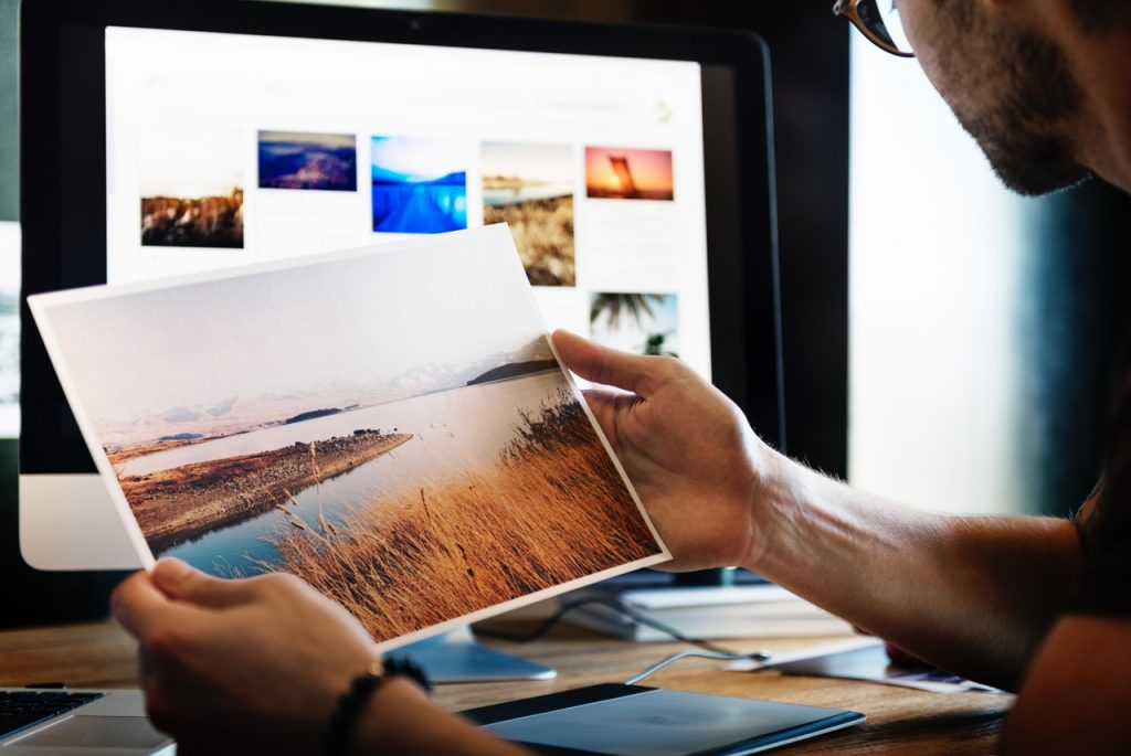 Person holding printed photo while staring in front of Mac