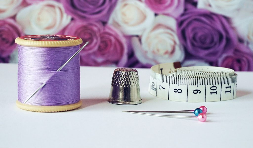 purple thread beside thimble and measuring tape