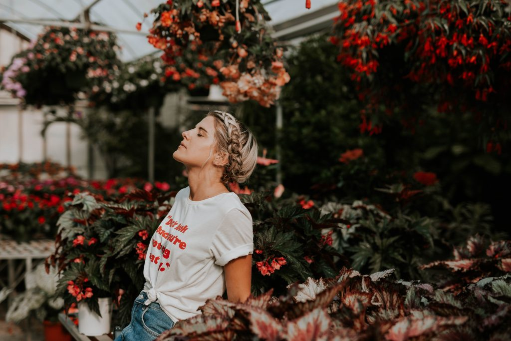 Woman in greenhouse wearing white shirt with knot