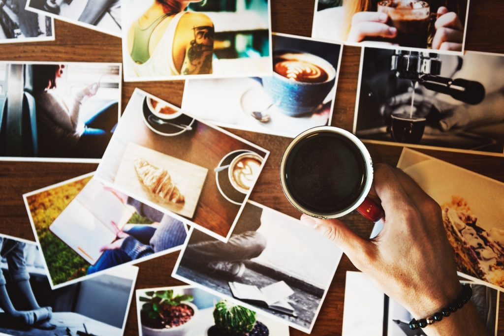 top view of person holding printed coffee on top of printed photos scattered on wooden surface