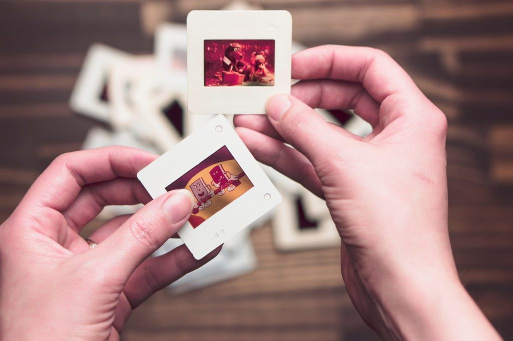 person holding small laminated photos in his hands