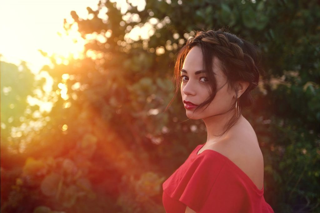 woman wearing red backless shirt and red lipstick standing beside trees at sunset